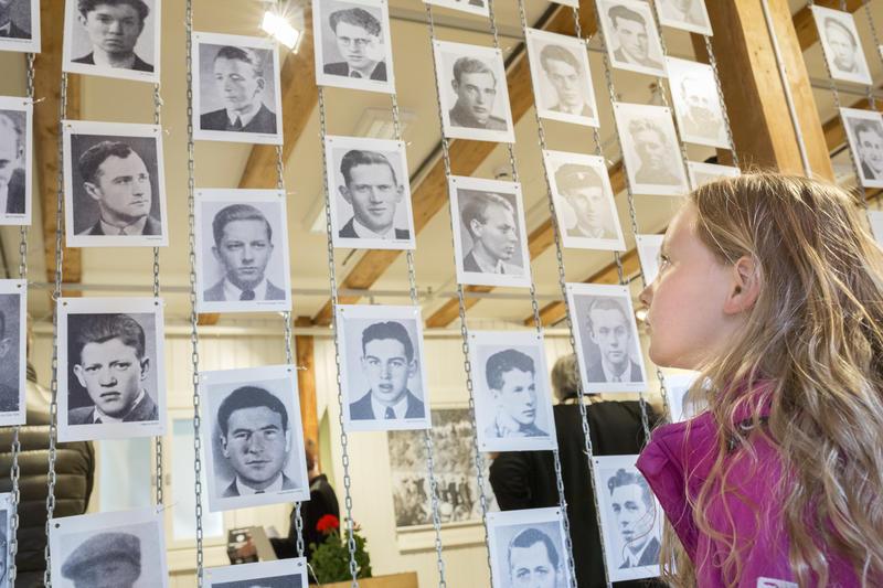 En jente ser på bilder i utstilling