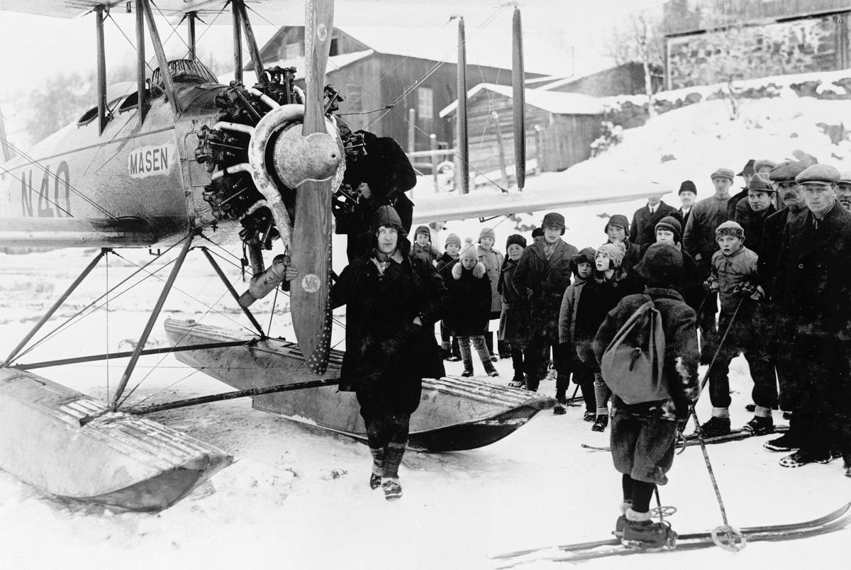 Repro, flypioneren Gidsken Jakobsen foran sjøflyet Måsen, N-40, på Mjøsisen, enmotors (stjernemotor), dobbeltdekker