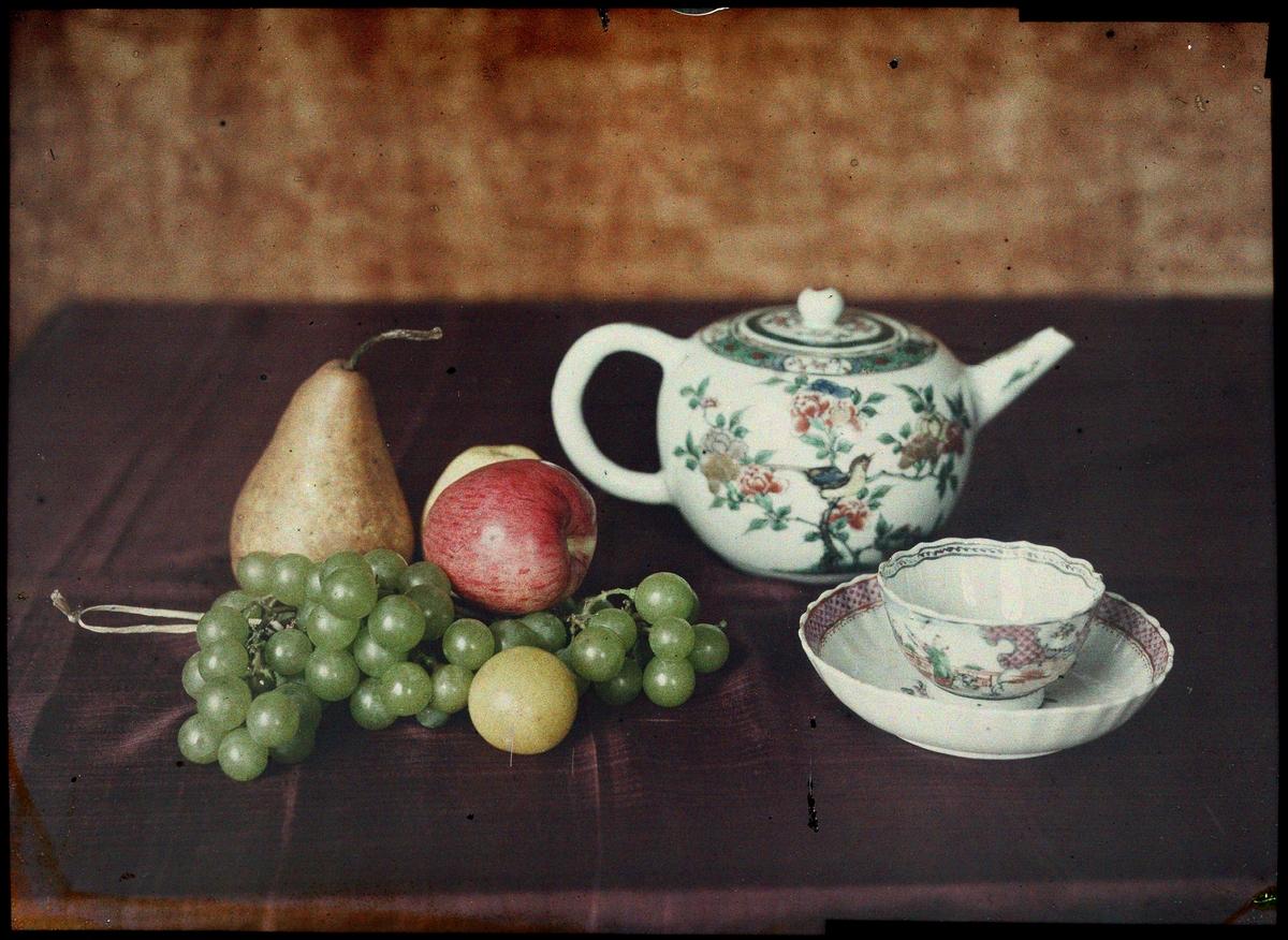 Lumière-autokrom. Stilleben. Tekanna, kopp, skål och frukter.