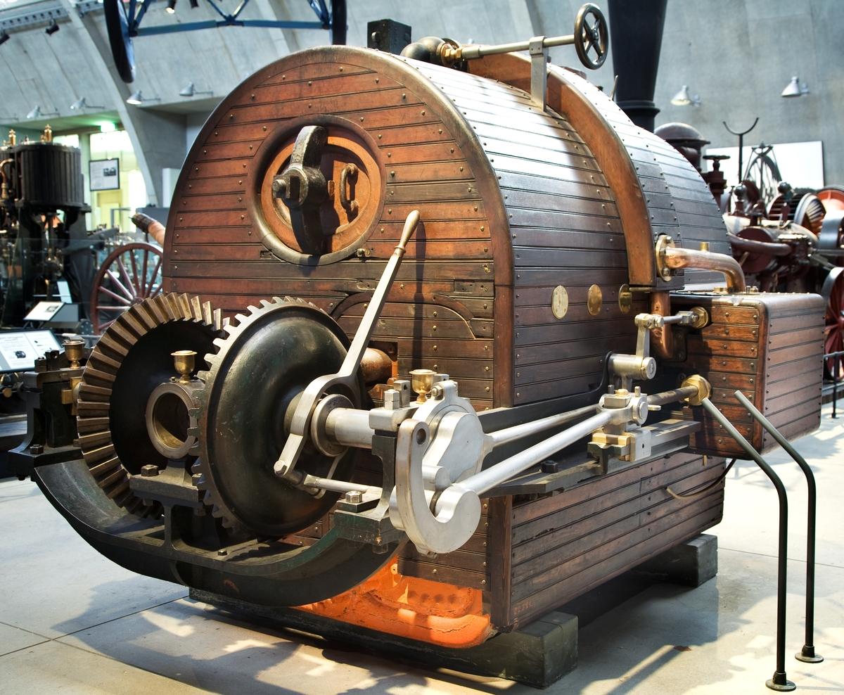 """Tvåcylindrig ångmaskin med rörpanna, med kugghjulskoppling för fram- och backgång. Vid föremålet knuten etikett: """"Gr.Q Nr 133"""".  Kugghjul, snedskuret. Diameter 370 mm. H: 135 mm. Vikt 27 kg. Tillbehör: Lösa delar: 2 lager, 2 bussningar (till propelleraxel med koniskt kuggdrev), smörjkopp. Härtill hör även 3 kranar, TM 22.525.Ritning till ångpanna till John Ericssons kanonbåt år 1868. 2 st. fotostatkopior, jämte negativ efter original i Sjöhistoriska Museet."""