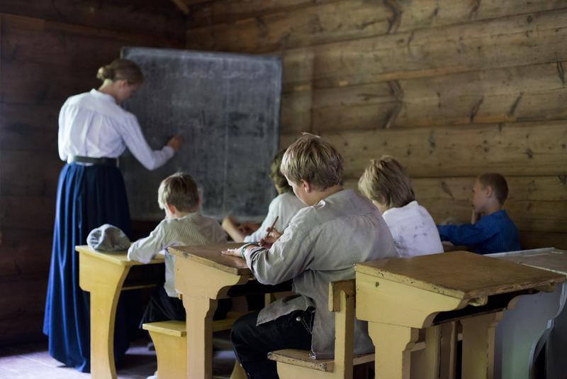 Barn sitter ved pultene i gammel skolstue mens lærerinne skriver på tavlen