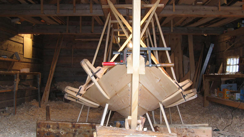 Clamps are used for holding the new strake in place before it is properly fastened. The sticks pointing down from the ceiling and up from the ground are used to shape the boat, by applying more or less pressure in different areas.