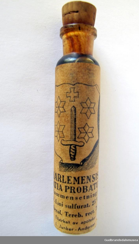 Medisinflaske med naturkork og papiretikett. Inneholder Haarlem olje, også kalt medicamentum gratia Probatum. Etiketten har en skjoldformet dekor med stjerner på sidene, et kors øverst og et sverd stående på hjaltet med spissen pekende opp.