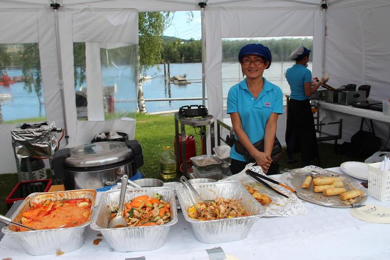 Foto av dame bak disk og fat med forskjellige ferdiglagde matretter.
