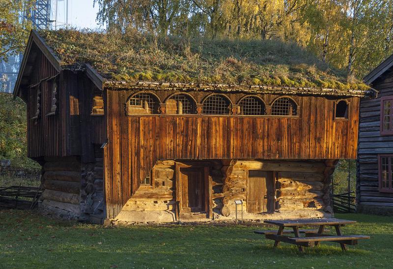 Brunlig tømmerbygning i to etasjer, med torv på taket og svalgang i andre etasje.