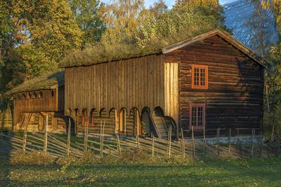 Grimsrudbygningen på Hedmarkstunet er en brunlig toetasjers tømmerbygning med to rutete vinduer over hverandre i gavleveggen og tettet svalgang i andre etasje.