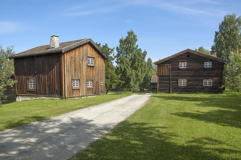 Grusveg som leder inn mellom to brunlige tømmerhus i to etasjer. (Foto/Photo)