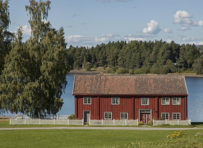 Stor, rød bygninge i to etasjer ligger bak et hvitt stakittgjerde ned mot vannet. På venstre side to bjørker.