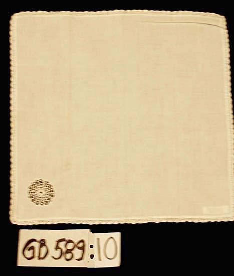 Näsduk (dam). Kvalitet: bomull. Vit med vit 5 mm bred virkad uddkant. Virkad, genombruten blomma  (40 mm i  diameter), isydd i ena hörnet.  Inskrivet i huvudkatalogen 1996-1997. Funktion: Näsduk för dam