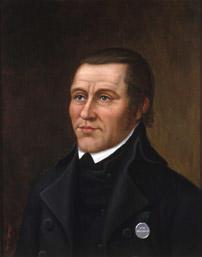 Portrett av Lars L. Forsæth  bakoverstrøket hår. Sort jakke med borgerdådsmedalje i sølv og i grønt bånd. Høyt gjenknappet sort vest, sort tørkle, hvit snipp. Brun bakgrunn. (Foto/Photo)