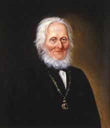 Portrett av Arnoldus v. W. S. Koren. Mørk drakt, medaljong (eller klokke?) i kjede rundt halsen (Foto/Photo)