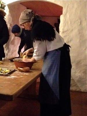 Dame med lyst skaut knyttet bak i nakken, svart sjal over hvis skjorte, og med blått fotsidt skjørt og forkle står og knar deig i en brun leirbolle på et stort bakstebord.