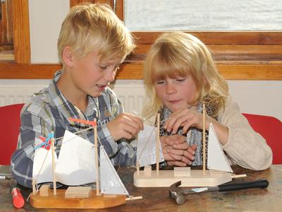 To barn i aksjon i Barnas båtverksted. Foran dem på bordet to lekebåter med seil, samt en hammer.