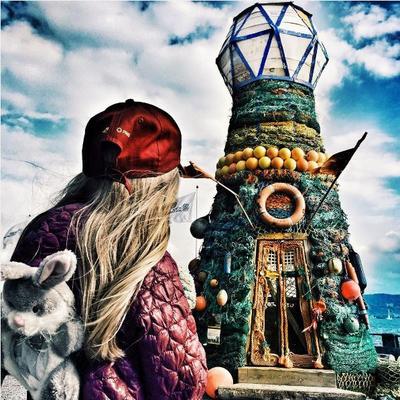 Fyrtårnet ved Norsk Maritimt Museum, laget av søppel fra havet. Barn med ryggen til i forgrunnen.