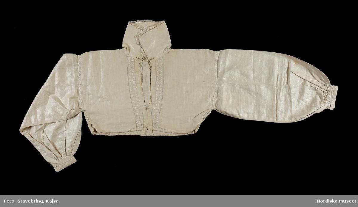 Överdel som suttit ihop med en nederdel, s.k. överdelssärk, av vit fin linnelärft, ett bålstycke med sidsömmar,  fodrat med grövre linne. Krage av ännu finare linne kantad med knypplad Vadstenaspets, Halsprund och längs med detta ända ner till kanten bård i rätlinjig plattsöm inom dubbla rader enkel utdragssöm med lingarn. Vidsydd ärm  med två längsgående sömmar, rynkad nedtill mot 2,5 cm bred ärmlinning , rynkorna översydda med smocksöm i sicksack. Både kring axelsömmen och på ärmlinningar bård i rätlinjig plattsöm. Ärmsprund med 2 motstående knapphål för en länkknapp, likaså uppe i halsen. I nederkanten är tyg och foder invikta och kastade mot varandra och har tidigare haft en söm mot nederdelen. Överdelen har glättats med glättsten så att den fått en vaxlik yta, vilket var fint.Bör därför inte tvättas. /Berit Eldvik 2010-06-10