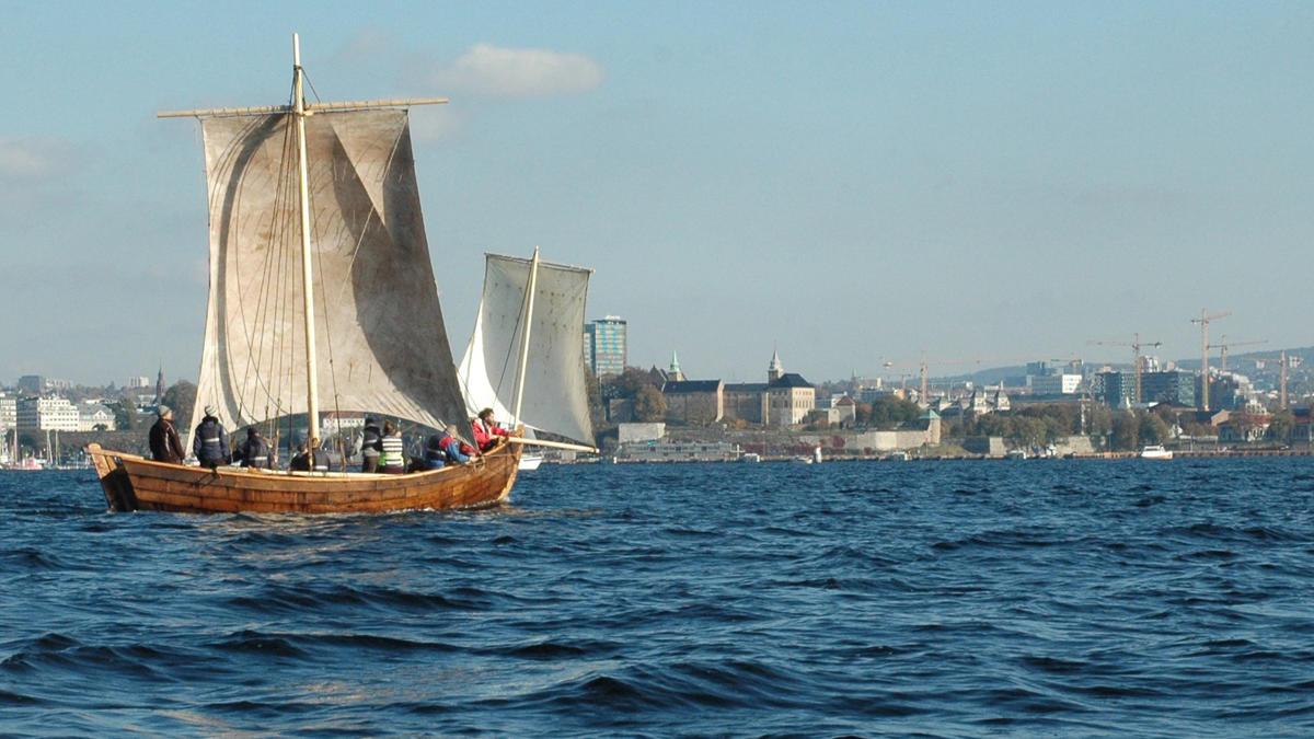 Trebåten Vaaghals på vannet med to seil, Oslo i bakgrunnen. Minst åtte personer ombord.