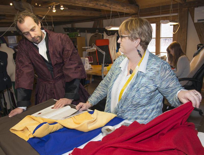 Mannen som skal få nytt kostyme blir vist stoffer i knalle farger av skredderen. (Foto/Photo)