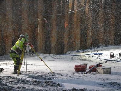 Arkeolog sikter inn totalstasjonen i snøvær.