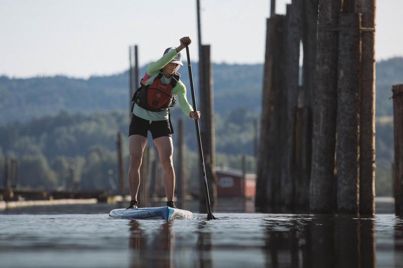 En person står på et padlebrett i fløtingsanlegget på Fetsund lenser