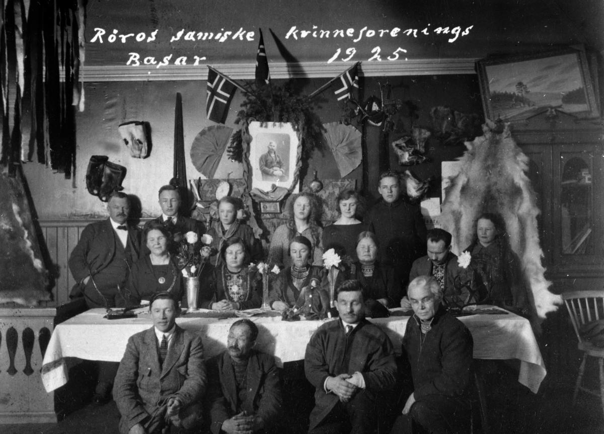 1925 nyjsenesiebrieh Røros samiske kvinneforening basaarem öörnedi Grønnsalesne Rørosesne. / I 1925 arrangerte Røros samiske kvinneforening basar i Grønnsalen på Røros. Duekesne, g.b./Bak, f.v.: Henrik Grønn, ovnohkens /ukjent, Solveig, Synnøve jïh/og Gunvor Grønn, hævvi vienth/ant. Øyvind Grønn. Buertiebealesne, g.b./Ved bordet, f.v.: Paula Grønn, Mali Holm, Jonetta Jonasen, Maja Anstensen, Martin Jonsson, ovnohkens/ukjent. Åvtene, g.b./Foran, f.v.: Nils Danielsen, Per Larsen Axman, Johan Anton Klemmetsen, Hinta Thomassen Liljestrand.
