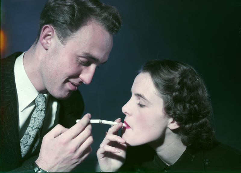 Reklamefoto fra Tiedemanns Tobaksfabrik. Mann tenner kvinnens sigarett.