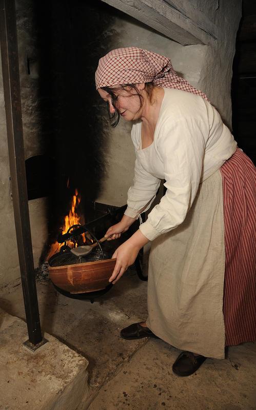 Kvinne med rød stakk, hvit langermet trøye, grått grovforkle og rødrutete skaut står foran den åpne ilden i grua og øser grøt fra ei stor gryte opp i en rundt trefat.