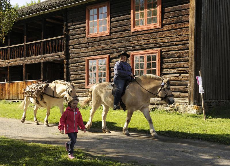 Lita jente som går ved siden av et tospann av hester den den førte blir ridd av en voksen mann og den bakerste bærer kløv. Gammelt, toetasjers tømmerhus i bakgrunnen.