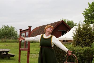 Rødhåret kvinne i middelalderdrakt, med kurv i hånda, slår ut med armene for å ønske velkommen til Urtehagen