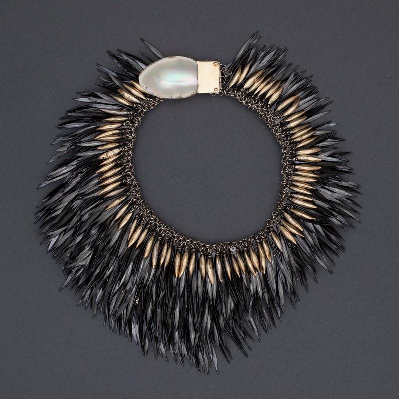 Halssmykke med brynje av sølv, hvorpå det er festet rader av flate, hammrede fjærlignende stålnagler. Også elementer av gull og perlemor langs den indre kanten. (Foto/Photo)