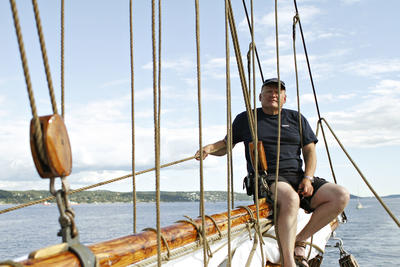 """Mann sitter i masta på skonnerten """"Svanen"""", land i bakgrunnen, klar himmel med litt skyer."""