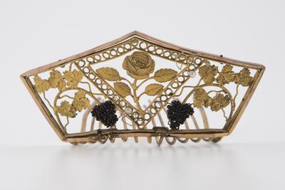 Hårkam fra 1800-tallet i kobber og forgylt messing. Dekorert med fremstillinger av rose og drueklaser.