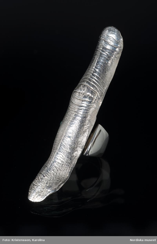 """Ring av silver, överdel i form av avlång avgjutning av fingerrygg. Underdel bestående bred ring med slits på ena sidan. Undertill graverad """"Cornelia"""". /Leif Wallin 2018-02-09"""