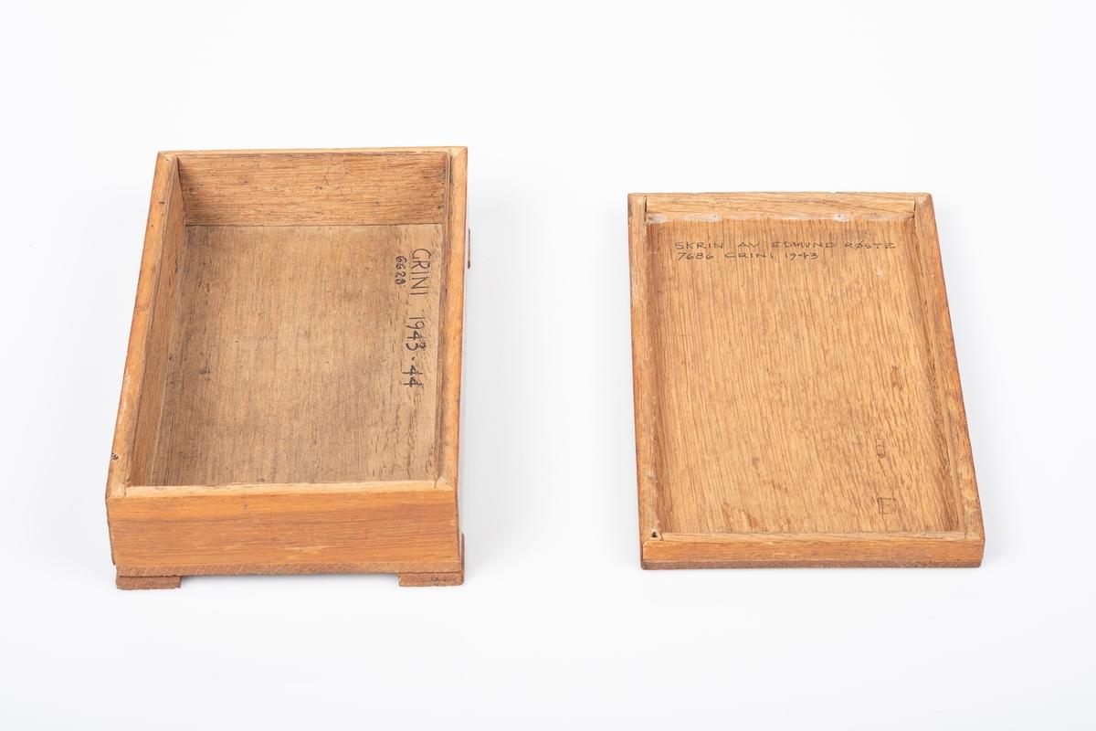 Skrin med lokk. Den er laget av tre og er lakkert. Den har fire kvadratiske ben. Lokket har utskåret dekor av akantus. Påskrift på innsiden av skrinet og lokket.