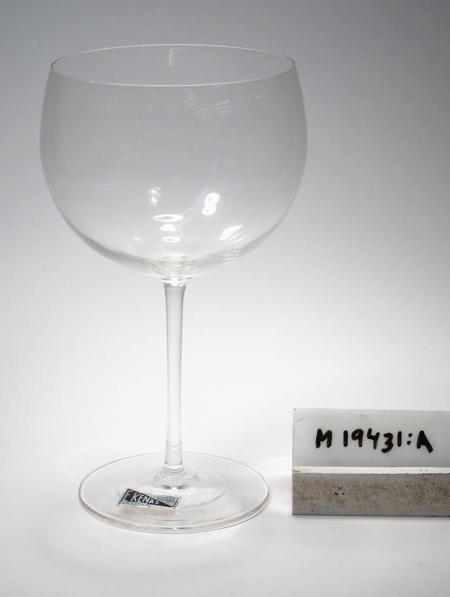Glas; Formgivet av John Orwar Lake. Beskrivning: Skål konvext avrundad nedåt med smalt, cylindriskt ben. Färg: Ofärgat, klarglas. Mått: Ovan anges höjd och  maxdiameter. Inskrivet i huvudkatalog: 1968. Funktion: Glas