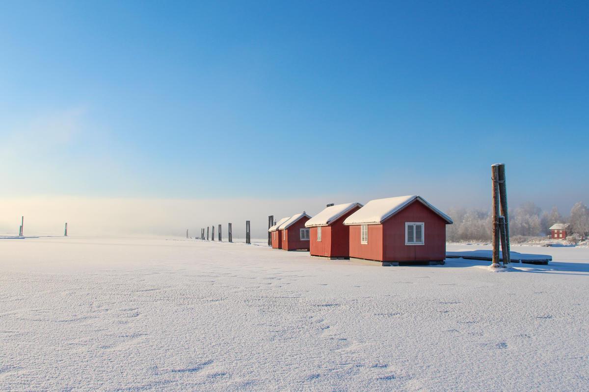 Foto av røde flytende hus på rekke på snødekket elv i fint vintervær.