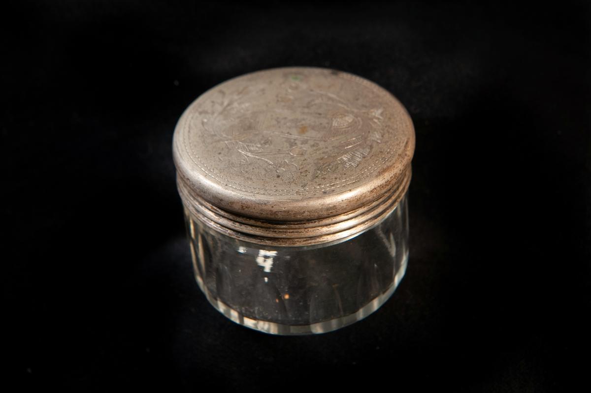 """Rund dosa i olivslipat glas. Runt lock av metall, graverat med blomslingor och namn: """"Wivi"""" på ett band. Locket troligen gjort av nickel eller nysilver. Ostämplat."""