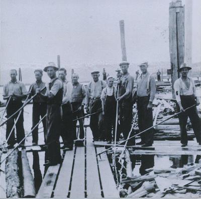 Gammelt foto av lensearbeidere med fløterhaker som poserer for foto ute på lenseanlegget i elva.. Foto/Photo