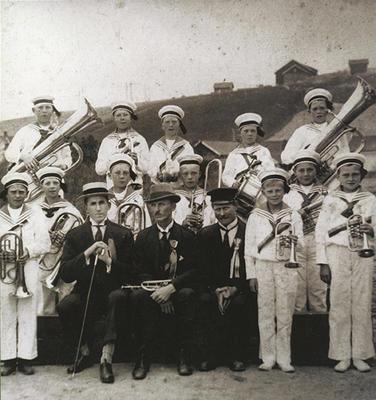 Gammelt foto av gutter med korpsuniform og instrumenter oppstilt sammen med tre eldre menn.