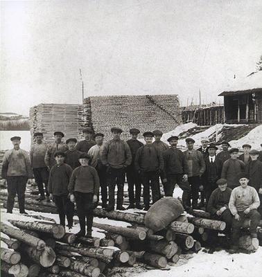 Gammelt foto av menn oppstilt i gruppe med stabler av sagvirke i bakgrunnen.