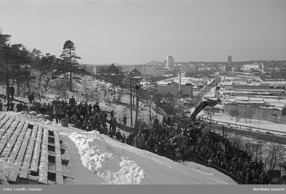 En tävling i backhoppning i Hammabybacken, Stockholm, backhoppare hoppar från en hoppbacke inför åskådare och domare, vy över Södra Hammabyhamnen och Södermalm.