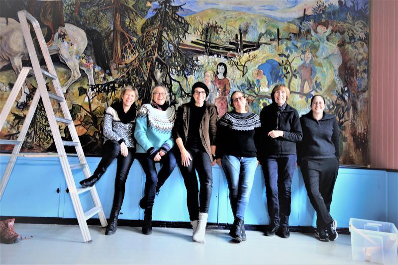 Maleriet er tilbake på fondveggen. En glad arbeidsgruppe foran verket. Foto: MiA.