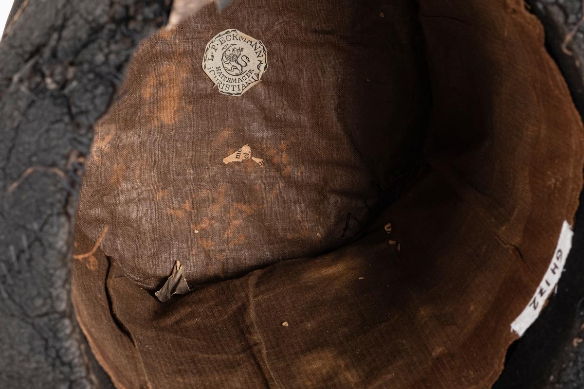 Svart flosshatt med høy pull og smal brem. De er foret med brun bomullstoff. Den har blitt lappet igjen flere steder.