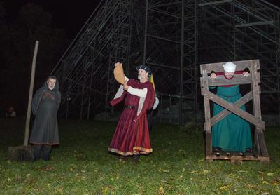 Bøddelen står til venstre, midt i bildet er en dommer i ferd med å lese opp urettene og straffen til ei av konene i kaupangen. Hun står i gapestokken.