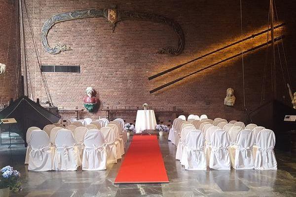 Sentralhallen i museet klargjort til bryllup, flere rader med hvitkledde stoler, en rød løper leder opp til et alter.. Foto/Photo