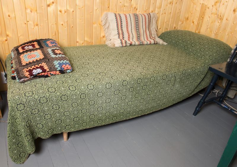 Divanen er hjemmelaget og det er trolig brukt understell fra en tysk feltseng fra 2. verdenskrig.