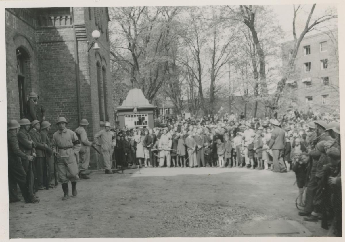 Frigjøringsdagene. 9. mai 1945, Folkemengde utenfor politikammeret, samt rikspolitifolk med hjelmer.