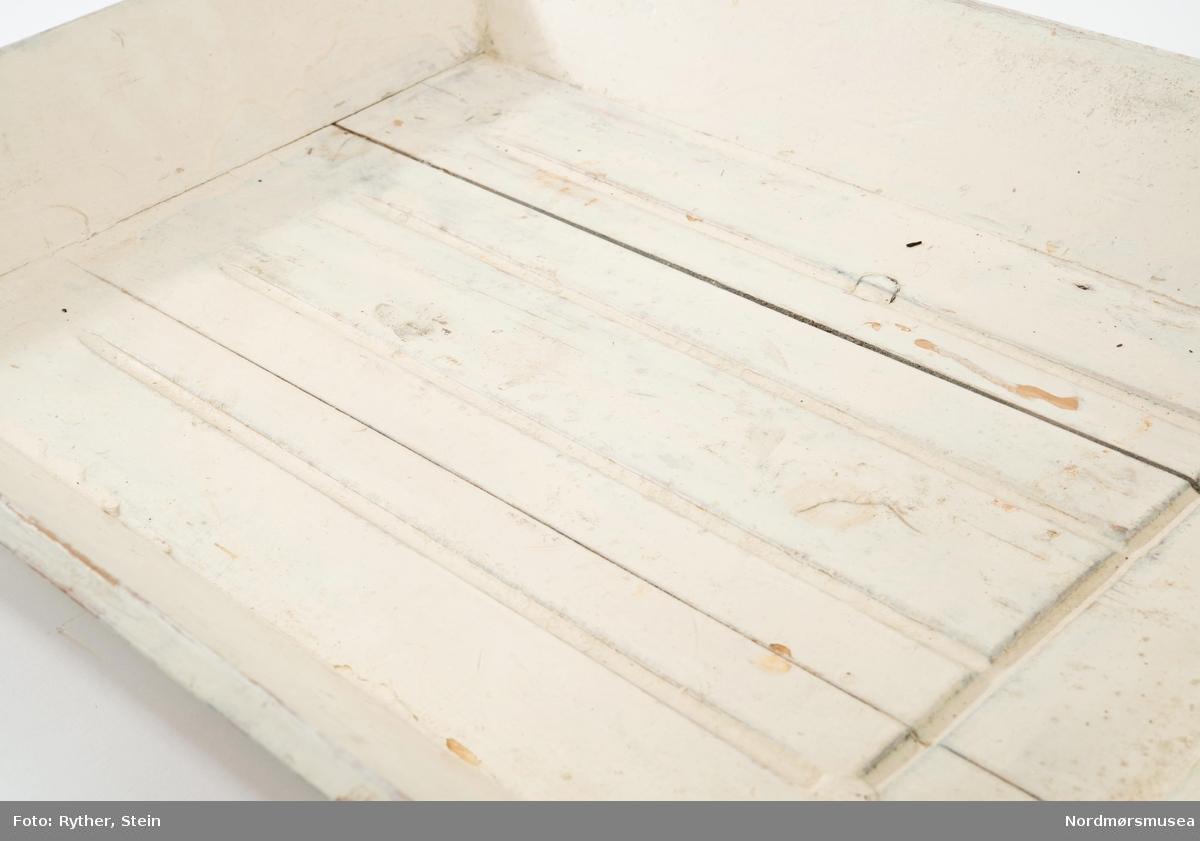 Til å sette fra seg etter oppvasken. Fra 1930åra. Fordypning innskåret i bunn, sannsynligvis for oppsamling av vann. Høy kant rundt.