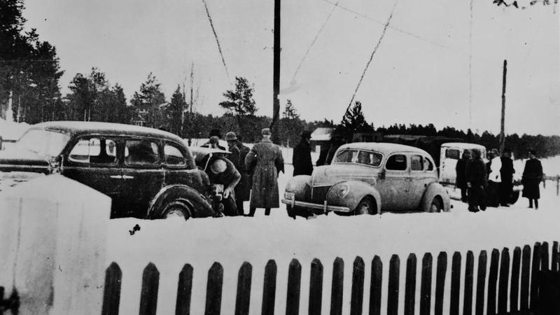 Biler, kongelige, politikere og flere ved den norsk-svenske grensa 12. april 1940. Foto fra Johnsen og Sæter: Kongens flukt.