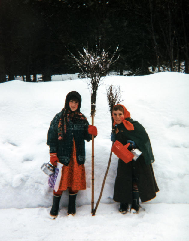 To jenter kledd ut som gamle kjerringer med skaut på hodet, står ved siden av hverandre og støtter seg på hver sin sopeline. I hånda holder de en kaffekjele og en kurv. (Foto/Photo)