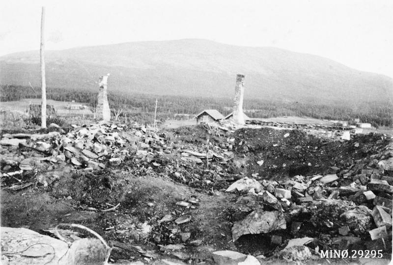 Noen av brannruinene på Os-garden, med Hummelfjellet i bakgrunnen. Foto: Anno Musea i Nord-Østerdalen, 29295.